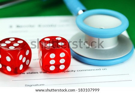 Two dice placed on a a doctors medical certificate pad next to his light blue stethoscope, asking the question do you gamble with your health care?  - stock photo