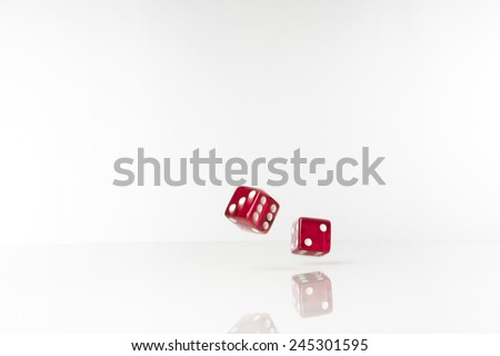 Two dice rolling along on white background with blur and movement - stock photo
