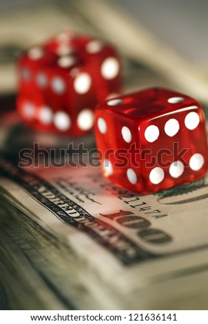 Two dices on money background - business concept. Very shallow focus.