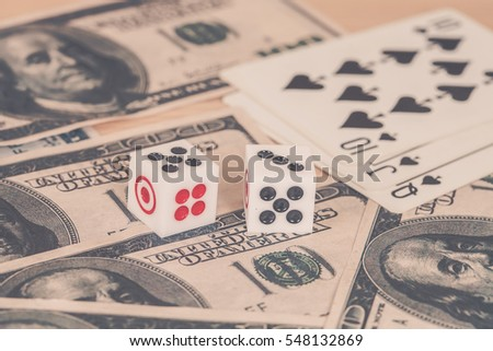 Two dices on wood table with US dollar and card