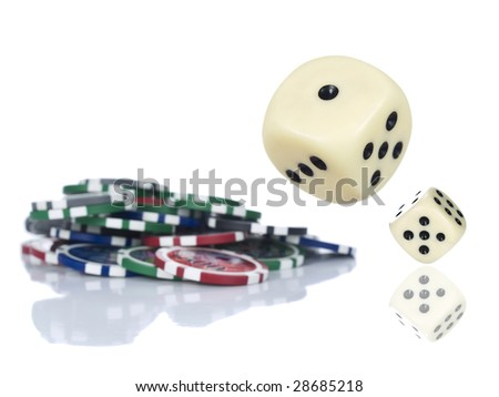 Two dices rolling beside some gambling chips. Isolated on white. - stock photo
