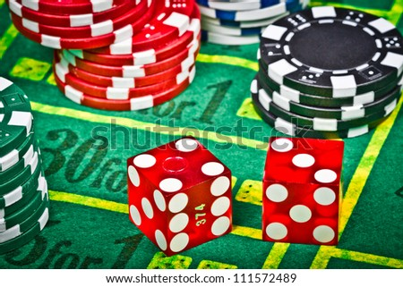 Two dices with seven over a green table with chips - stock photo