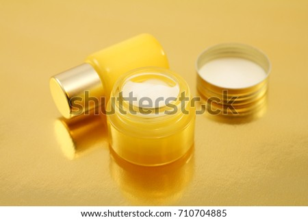 Two different blank jars of cream with reflections on a golden background