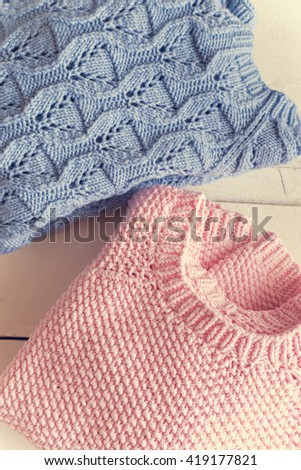 two different  cozy knitted sweaters on white background