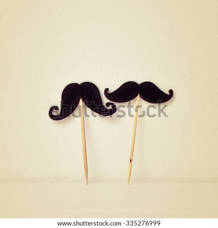 two different felt mustaches in sticks over a beige background, with a retro effect - stock photo