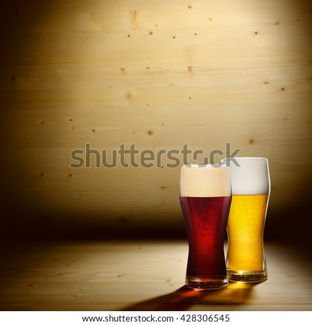Two different glasses of beer on wood background with copyspace