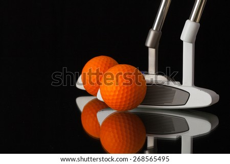 Two different golf putters and balls on a black glass desk - stock photo