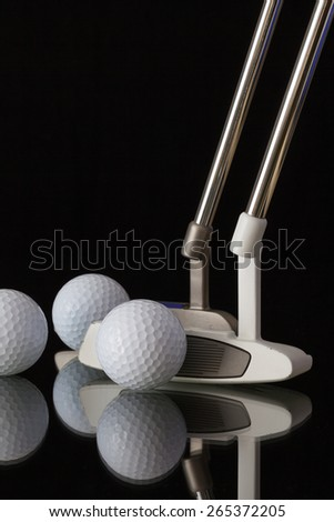 Two different golf putters and three balls on a black glass desk - stock photo