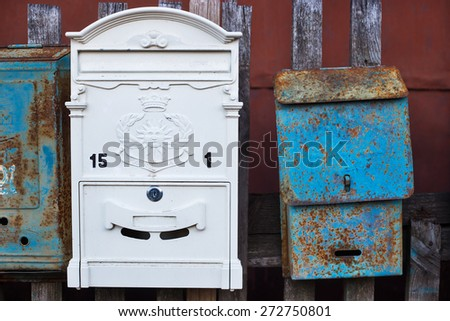Two different mailboxes: new white and old with rust attached to the fence - stock photo