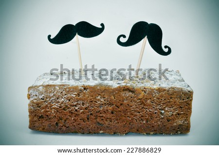 two different moustaches stuck in a piece of cake - stock photo