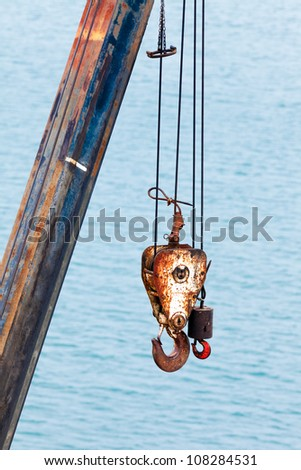 Two different sized battered and rusted hooks and cables of crane for hoisting or lifting heavy loads in harbor against blurry ocean background - stock photo