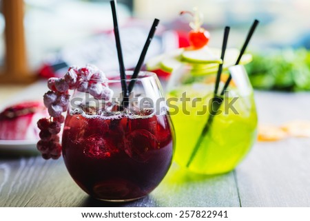 two different soft lemonade cherry and apple in a glass on a wooden table with decorations focus on different parts of the glass - stock photo