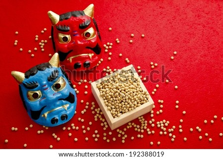 Two differently colored devil masks next to pellets in a box. - stock photo