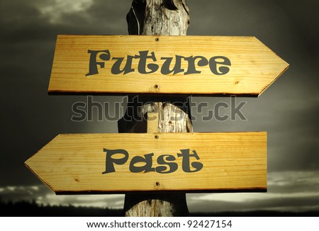 Two directional arrows that indicate the past and the future with a dramatic sky - stock photo