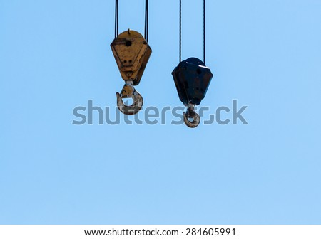 Two dirty industrial crane hoist hooks and pulleys hanging by steel cables on pale blue sky. - stock photo