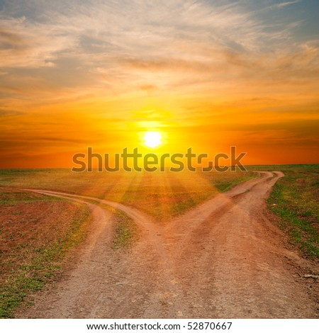 two dirty ways under sunrays. sunset time - stock photo