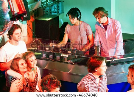 Two disc jockeys at work in the DJ booth at a club - stock photo