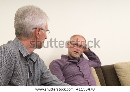 Two discussing seniors at home. - stock photo