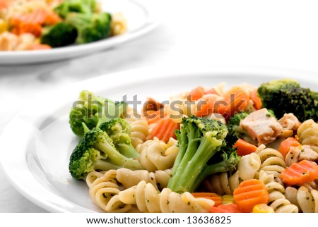 Two dishes of pasta with mixed vegetables
