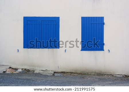 Two dissimilar windows closed by blue shutters on a white wall - stock photo