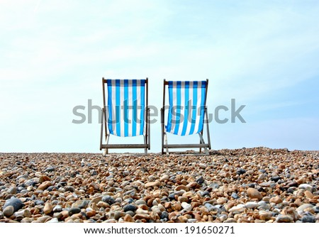 Two distant deck chairs on a pebble beach, looking out towards the horizon. - stock photo