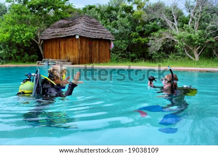 Two divers exercising in training pool. Shot in Sodwana Bay, KwaZulu-Natal province, Southern Mozambique area, South Africa. - stock photo