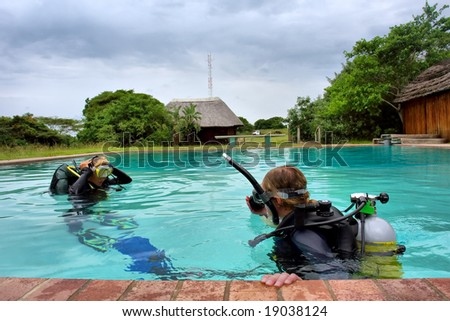 Two divers in training pool under storm skies. Shot in Sodwana Bay, KwaZulu-Natal province, Southern Mozambique area, South Africa. - stock photo