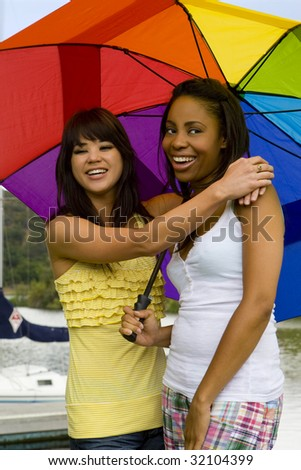Two diverse friends playing under a rainbow umbrella - stock photo