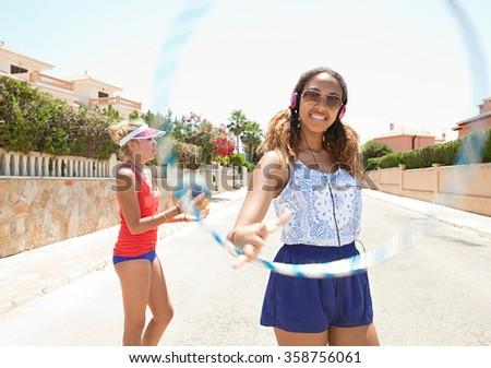 Two diverse teenager friends enjoying a summer holiday together in a suburban street having fun, sporty with basketball, hoola hoop and headphones technology. Retro adolescent lifestyle outdoors. - stock photo