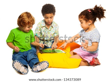 Two diversity looking boys and girl playing with tablet computer sitting on pillows