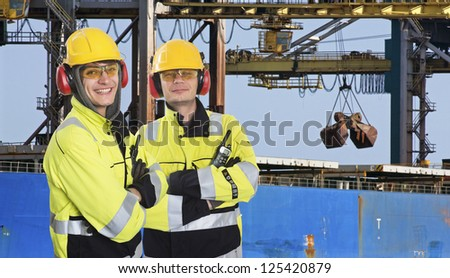 Two dockers, coworkers and colleages, wearing the same outfit, posing in front of a large transport ship, where raw materials, such as iron ore are being unloaded at an industrial harbor - stock photo
