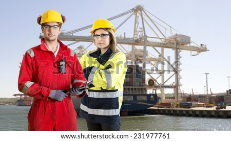 Two dockers, wearing safety gear, protection and work clothing, posing in front of a large container ship in an industrial harbor - stock photo