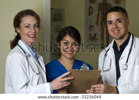 Two doctors and nurse discussing lab results stop and smile at the camera.