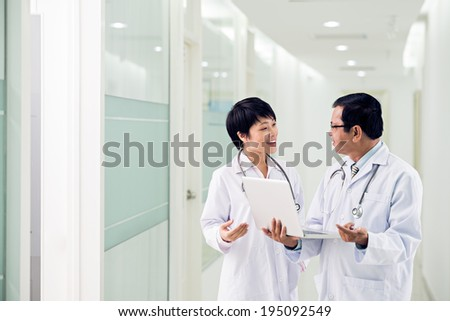 Two doctors discussing diagnosis while walking - stock photo