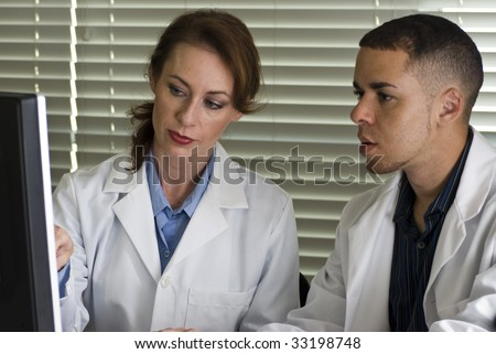 Two doctors discussing information they see on their computer monitor.