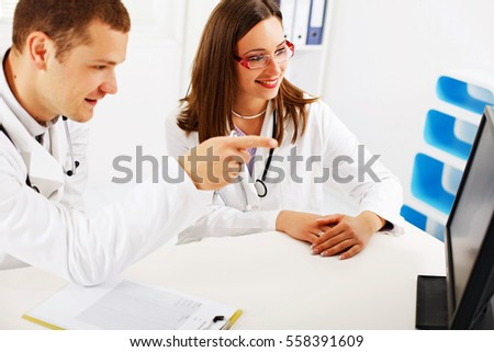 Two doctors discussing, sitting at the office.