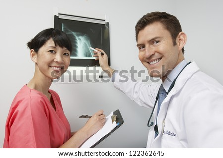 Two doctors discussing X-ray report in hospital - stock photo