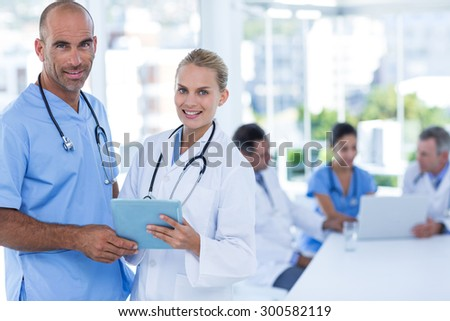 Two doctors holding clipboard while their colleagues working in medical office - stock photo