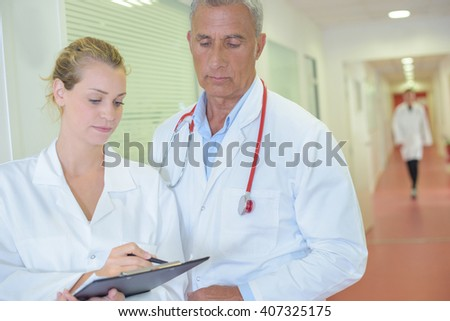 Two doctors looking at clipboard in hospital corridor