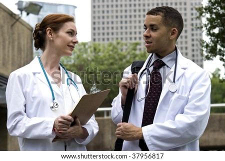 Two doctors on break in a city green space, engaged in friendly conversation. - stock photo