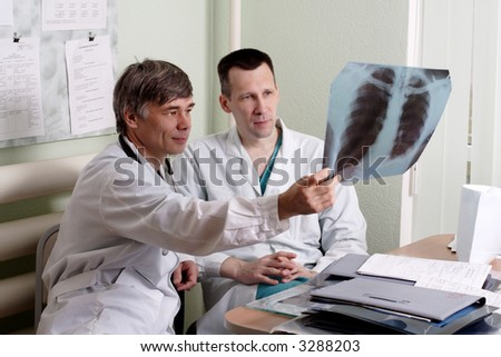 Two doctors review some case notes. - stock photo