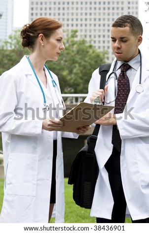Two doctors reviewing a chart outside with the medical center in the background. - stock photo