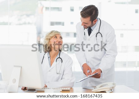 Two doctors using digital tablet by computer at medical office