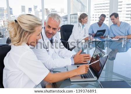 Two doctors with a laptop in a bright office - stock photo
