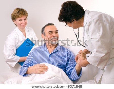 Two doctors with a patient - stock photo