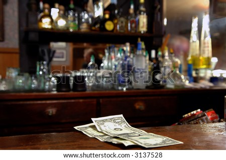 Two Dollar Tip Left For Bartender in Rustic Bar.  Very shallow depth of field. - stock photo