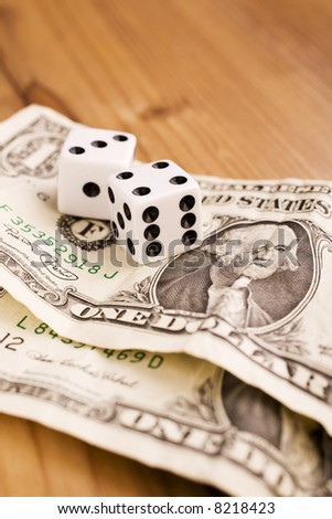 Two dollars and two dices on the wooden table
