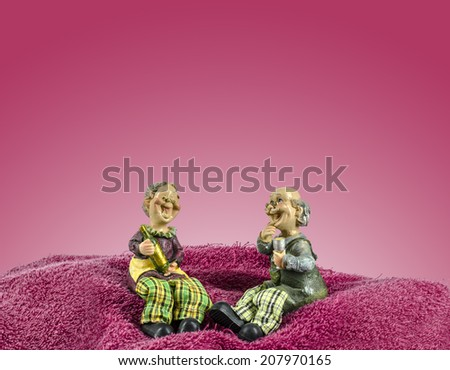 Two dolls which made like grand mom & grand dad sit on towel mountain - stock photo