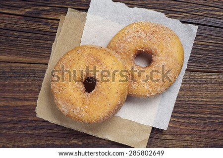 Two donuts on a wooden table closeup, top view - stock photo