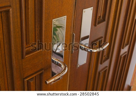Two door handles to contemporary front door in mahogany